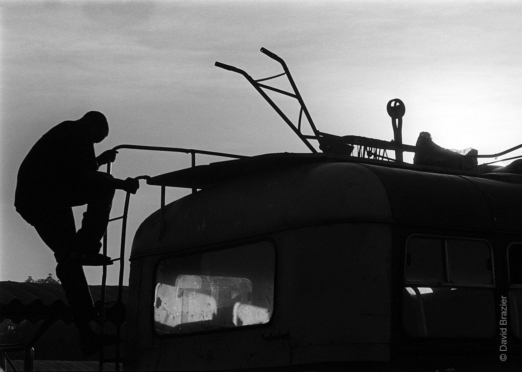 Black and white sihouette image of man climbing off the roof of a bus
