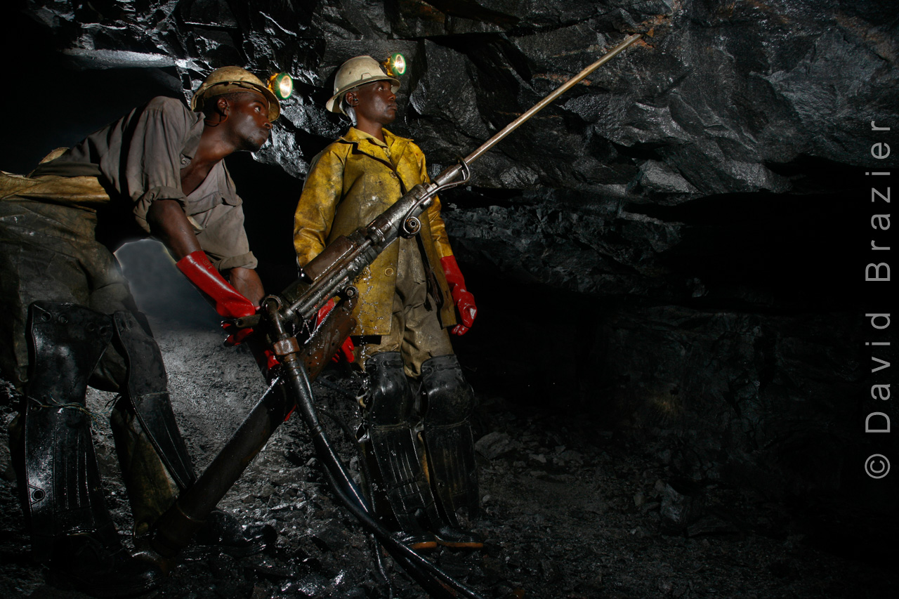 African gold miners using a drilling machine to mine gold underground