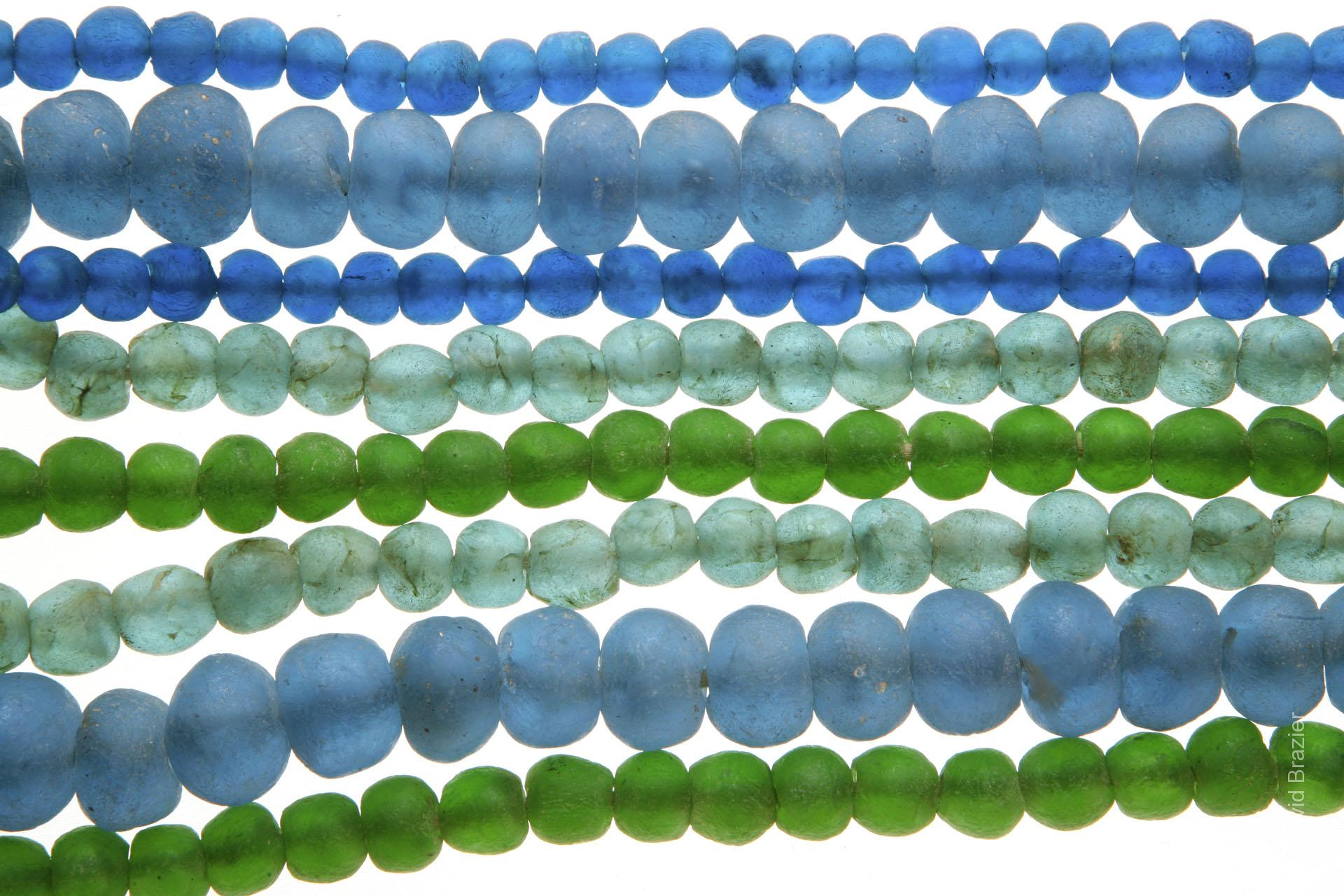 Blue and green recycled glass beads on white background