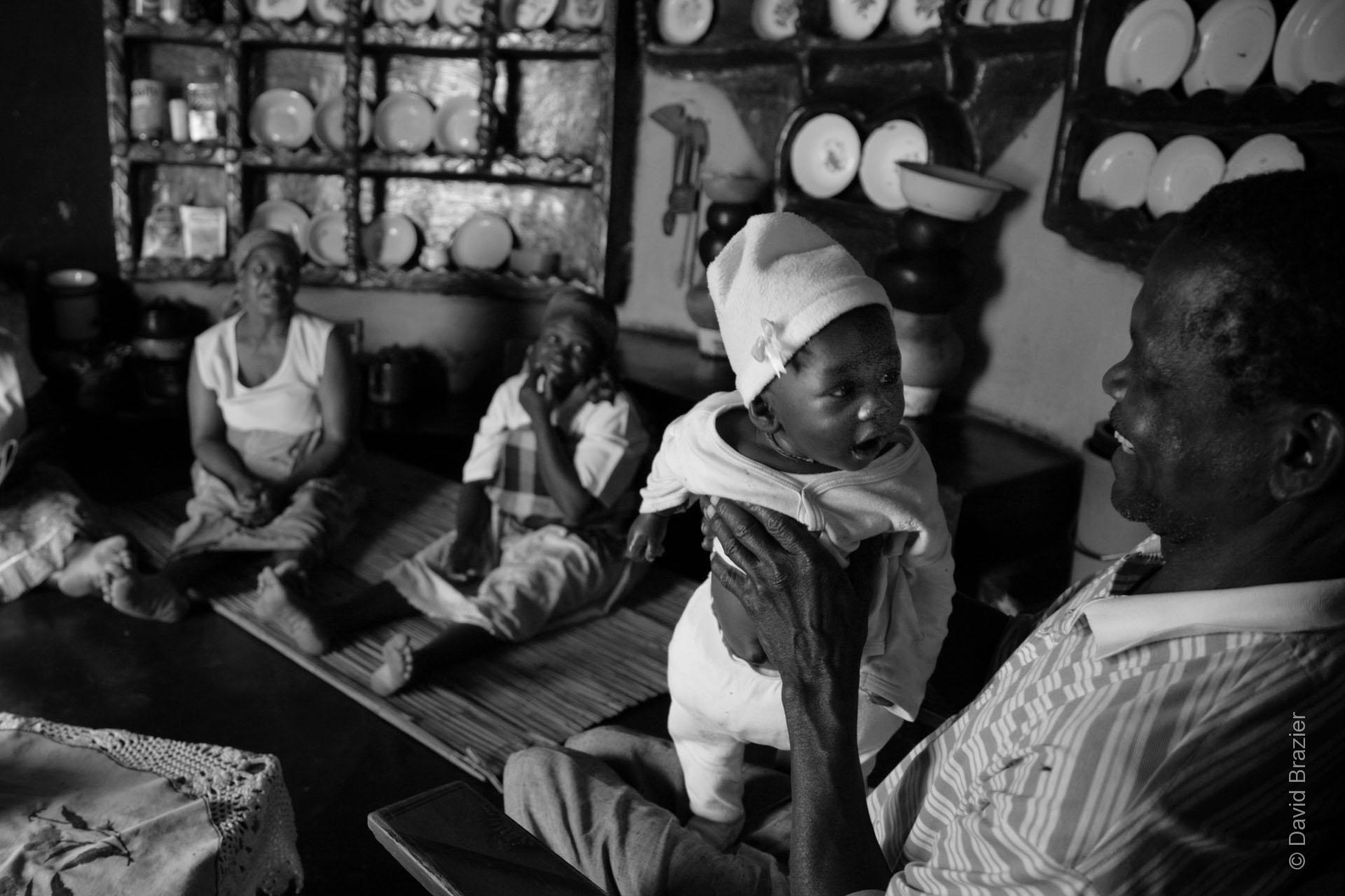 Black and white image of grandfather holding a baby in an African kitchen