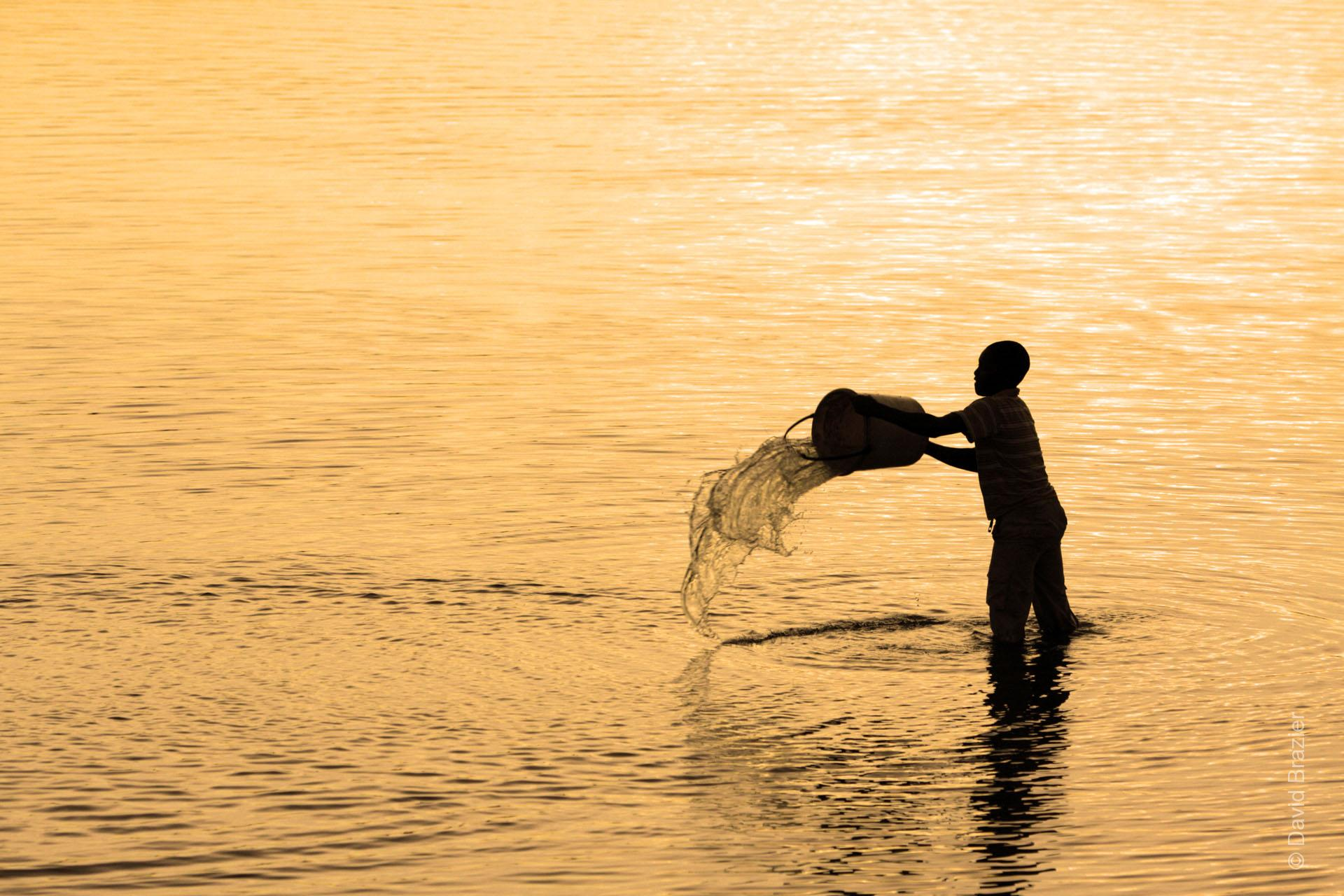 African boy standing in a dam at dusk, throwing water from a bucket