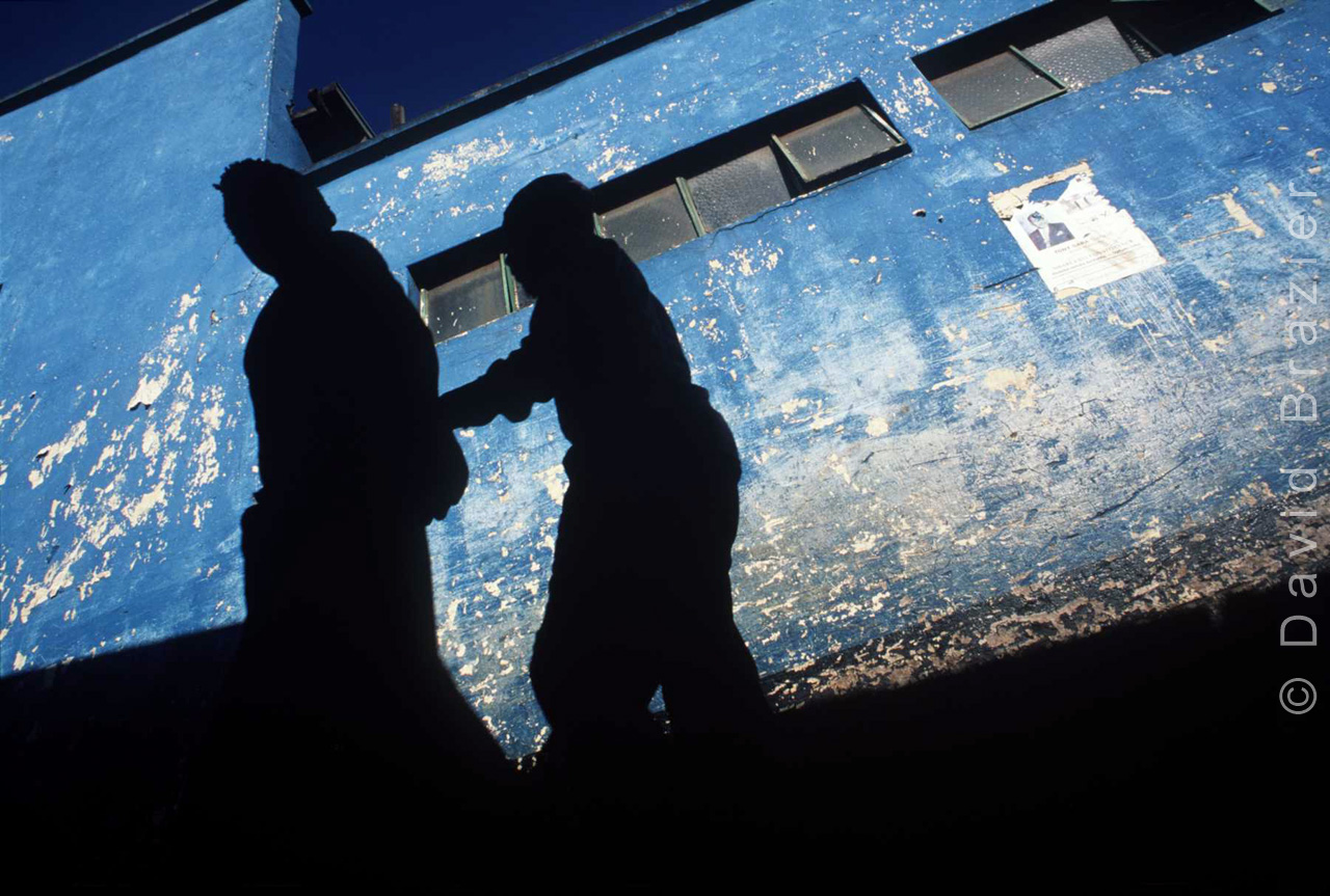 Silhouette image of a blind beggar being led by another against a fadedblue wall
