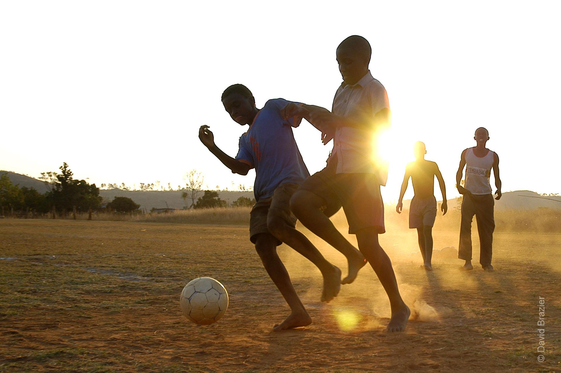 African boys playing football at dusk