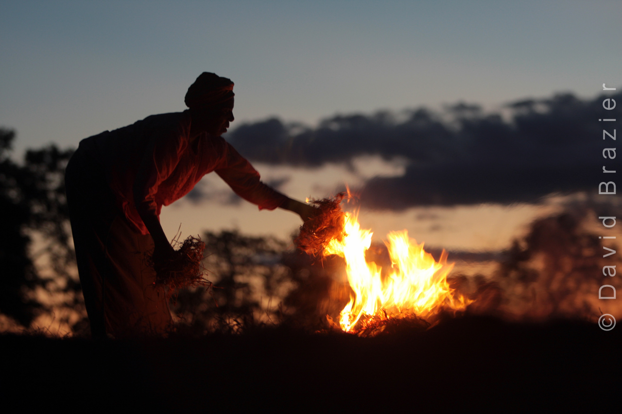 African woman burning crop residues in a fire at dawn