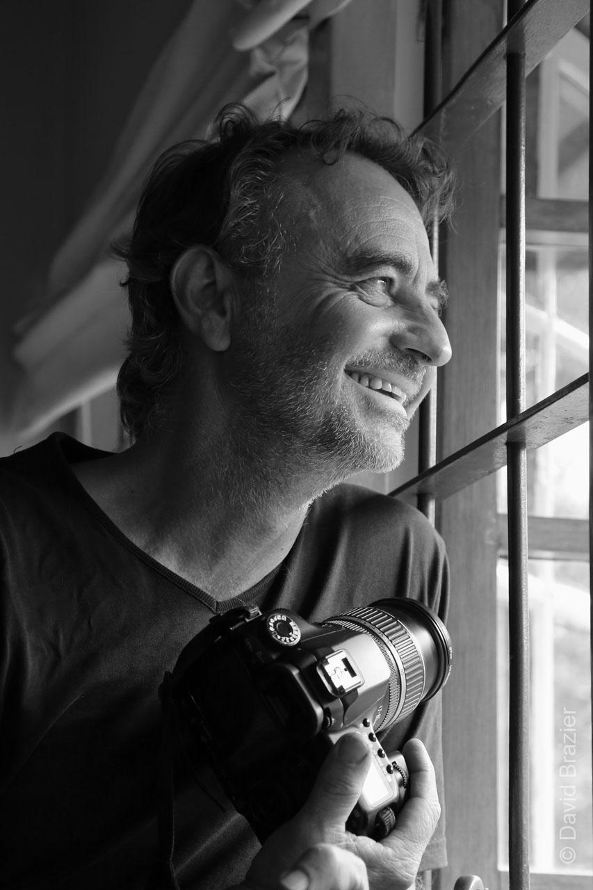 David Brazier holding camera by window