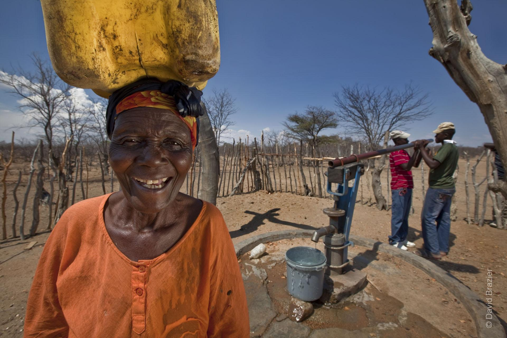 African woman carrying water on her head with men at a pump in the background