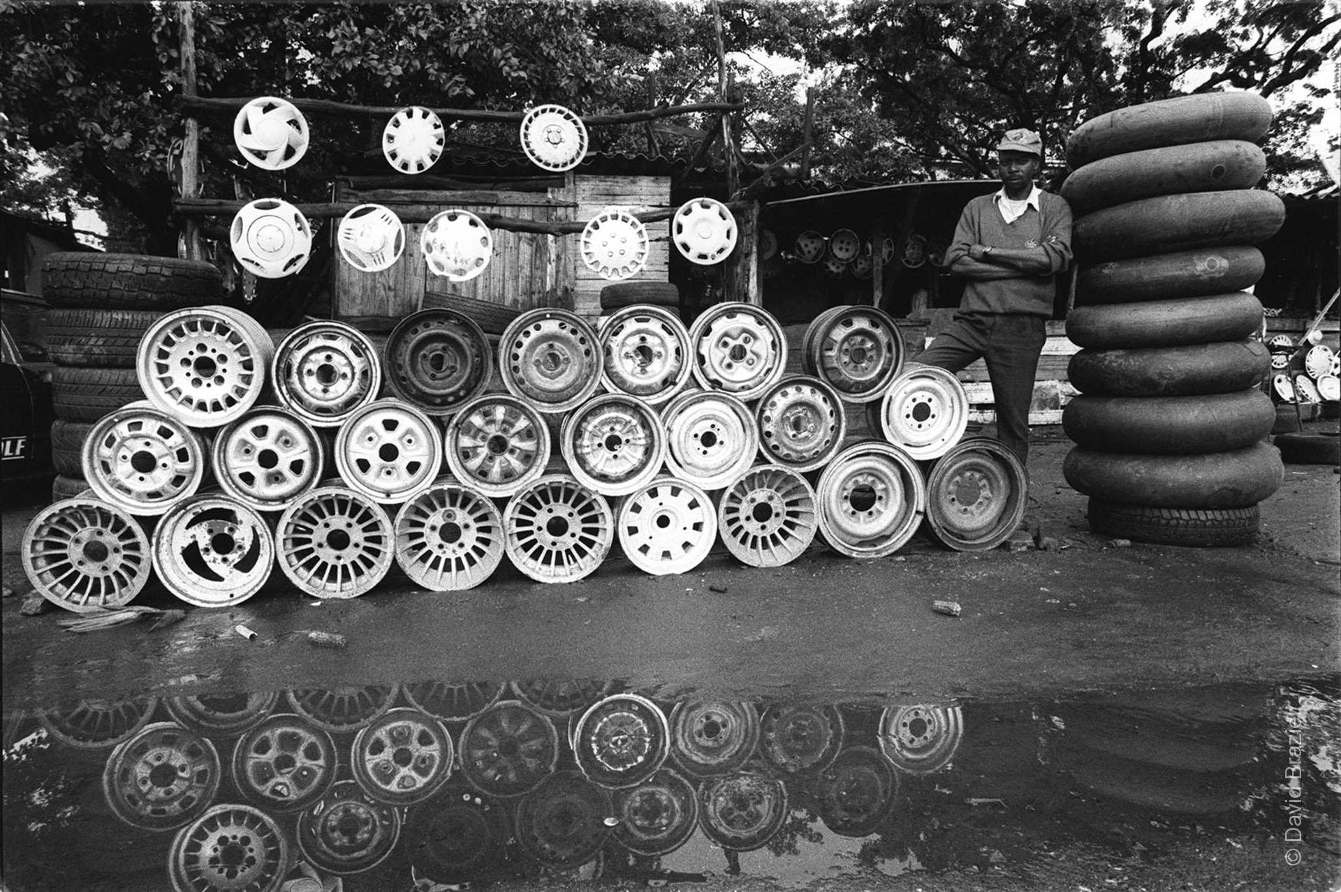 African man selling hub caps on the roadside