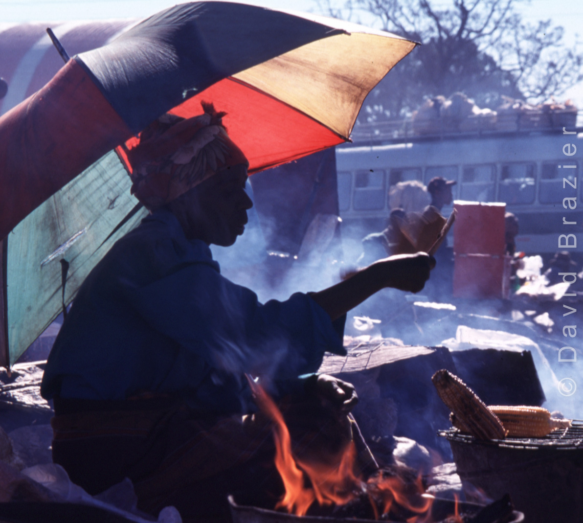 African woman selling roasted maize on roadisde with colourful umbrella